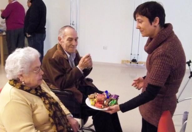6.- Ofreciendo los dulces navideños a los ancianos residentes.