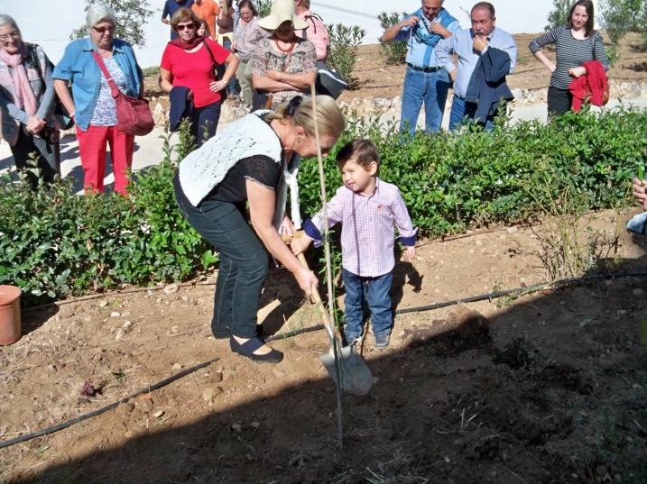 La hermana de Paco Marín y su nieto plantando el mezquite en Arriate.