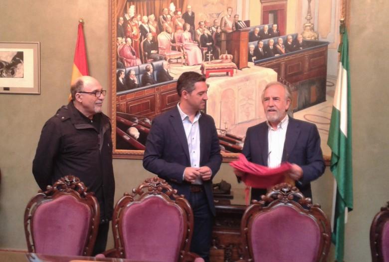 Adolfo Fernández Palomares, Director General de Parques y Jardines, le hace entrega de la bandera de Sevilla para que presida el acto de hermanamiento.