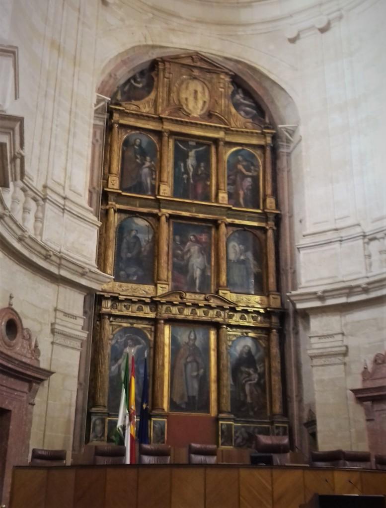Retablo de la antigua iglesia renacentista, desacralizada, en las sesiones parlamentarias, se cubre con el escudo de Andalucía.